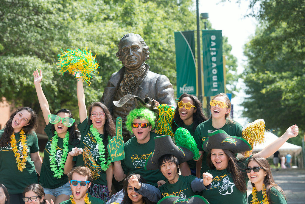 """Incoming freshman students pose at the Mason Statue as the Office of Orientation and Family Programs and Services hosts Freshman Orientation at the Fairfax Campus. Photo by Alexis Glenn/Creative Services/George Mason University"""